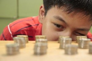 A boy examines stacks of coins