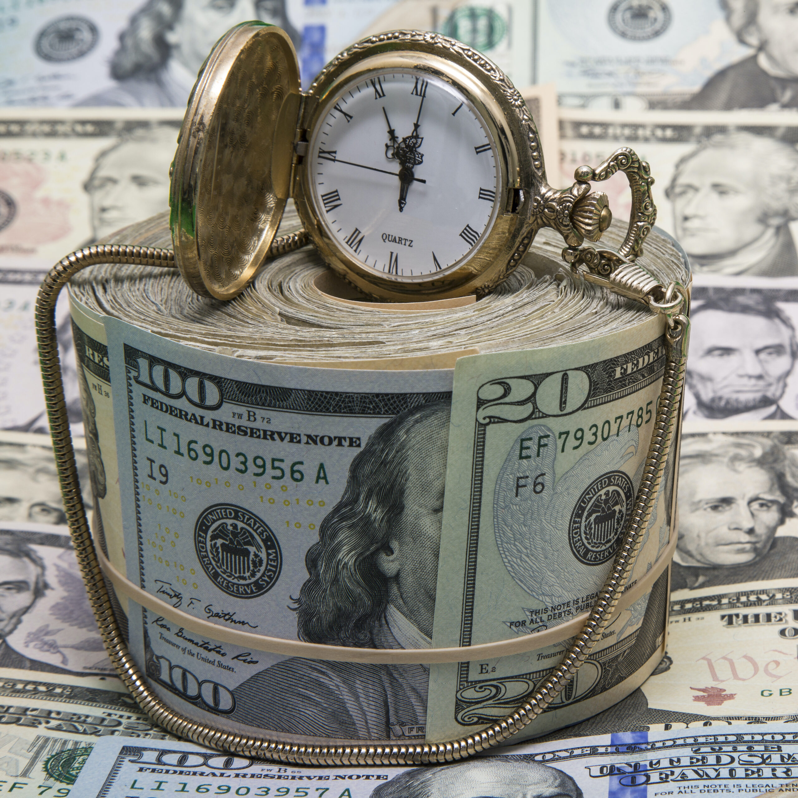 A gold watch sitting on a pile of money